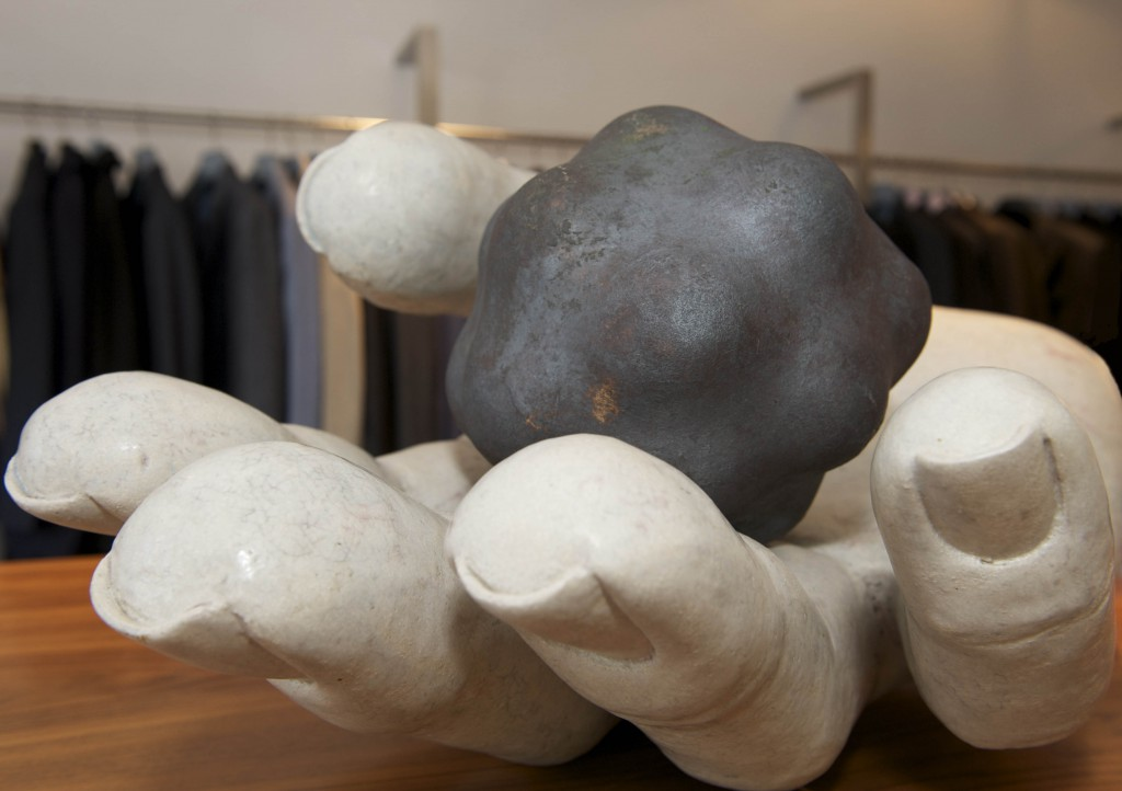 ceramic sculpture of hand and molecule